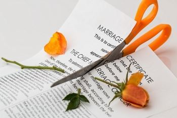 Marriage Certificate and a Rose Being Cut by a Pair of Scissors | Divorce & Immigration Blog